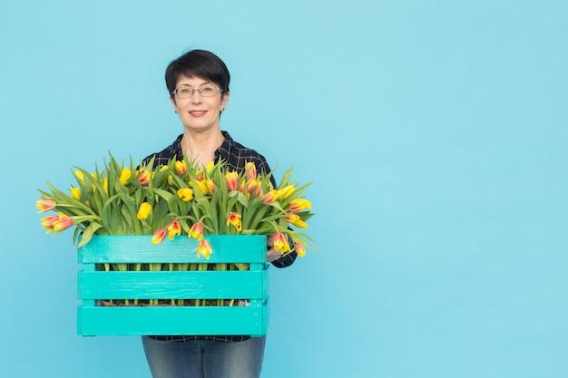Gelukkige vrouwenbloemist die van middelbare leeftijd glazen met doos tulpen op blauwe achtergrond met exemplaar dragen