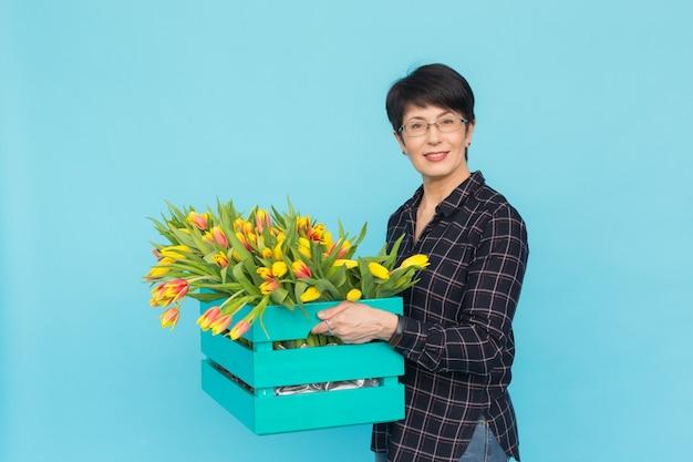 Gelukkige vrouwenbloemist die van middelbare leeftijd glazen met doos van tulpen op blauwe achtergrond dragen