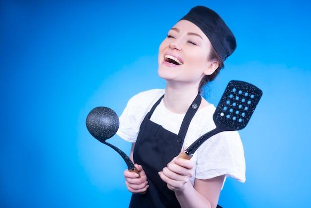 Gelukkige vrouwenchef-kok die en keukengerei in haar handen lachen houden tegen blauwe muur