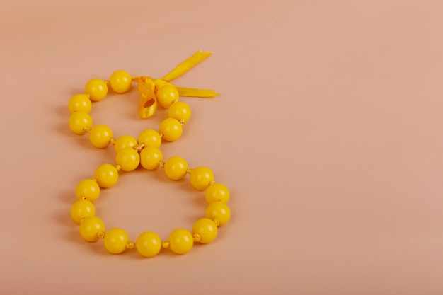 Gelukkige vrouwendag, met gele kraal en boog, acht maart, 8 maart op papier