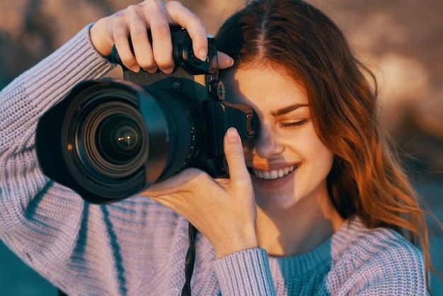 Gelukkige vrouwenfotograaf buiten in het professionele landschapsmodel van de bergen