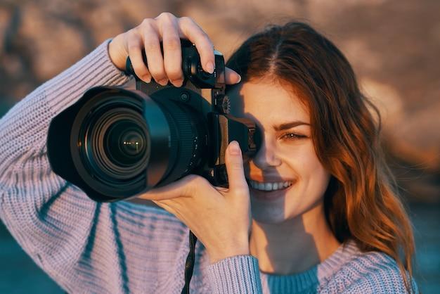 Gelukkige vrouwenfotograaf buitenshuis in het professionele landschap van bergen