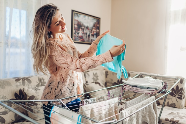Gelukkige vrouwenhuisvrouw die schone kleren op droger hangen na thuis het wassen