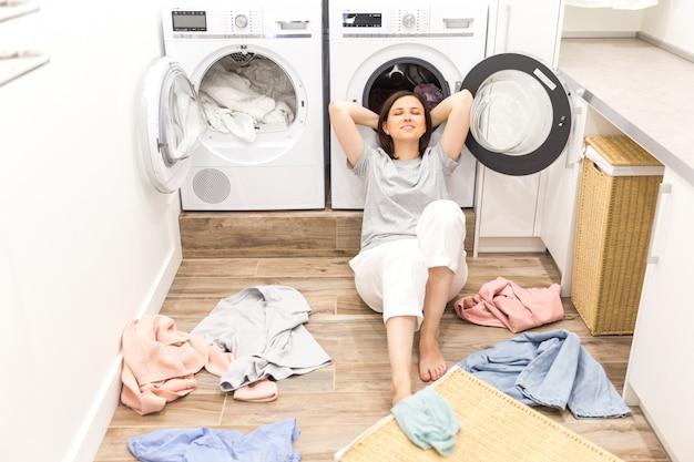 Gelukkige vrouwenhuisvrouw in de wasruimte dichtbij de wasmachine met vuile kleren