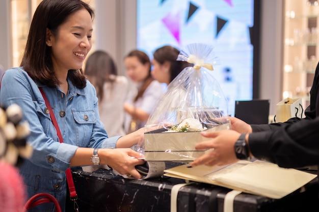 Gelukkige vrouwenklant die gift en bloemdoos ontvangen die van winkelmanager wordt geplaatst.