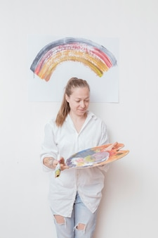 Gelukkige vrouwenkunstenaar met palet en borstel in workshop