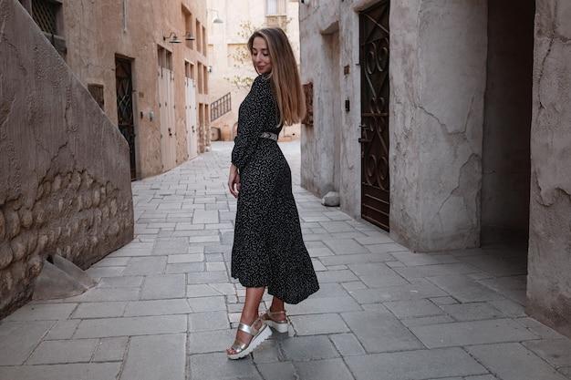 Gelukkige vrouwenreiziger die zwarte kleding draagt die door de straten van een oude arabische stad of een dorp in het midden van de woestijn loopt. concept van toerisme en avonturen in al seef dubai
