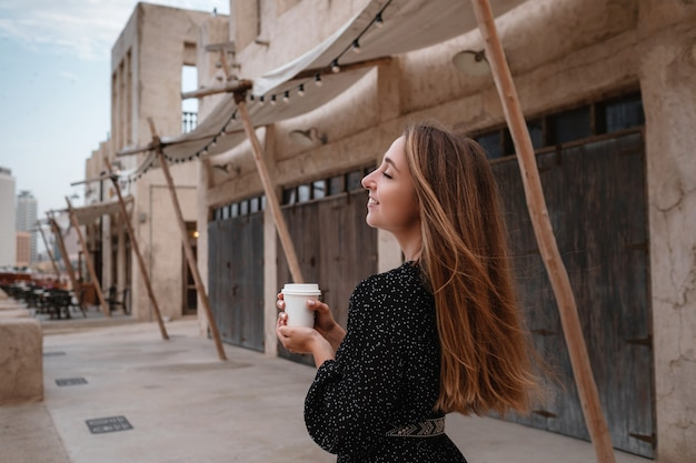 Gelukkige vrouwenreiziger die zwarte kleding draagt die door de straten van een oude arabische stad of een dorp in het midden van de woestijn loopt. koffie in een witte kop, genietend van traditionele arabische koffie