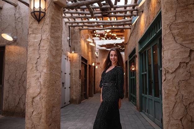 Gelukkige vrouwenreiziger die zwarte kleding draagt die door de straten van een oude arabische stad of een dorp in het midden van de woestijn loopt. traditionele arabische olielampen in de straat al seef dubai Premium Foto