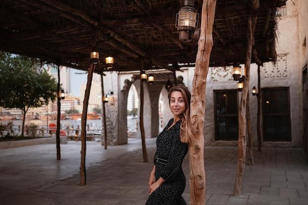 Gelukkige vrouwenreiziger die zwarte kleding draagt die door de straten van een oude arabische stad of een dorp in het midden van de woestijn loopt. traditionele arabische olielampen in de straat al seef dubai