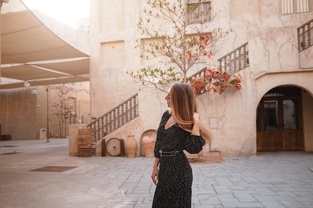 Gelukkige vrouwenreiziger die zwarte kleding draagt die door de straten van een oude arabische stad of een dorp in het midden van de woestijn loopt.