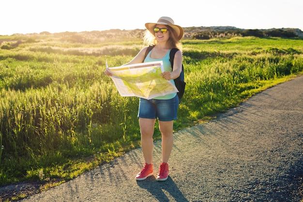 Gelukkige vrouwenreiziger met rugzak controleert kaart om richtingen te vinden