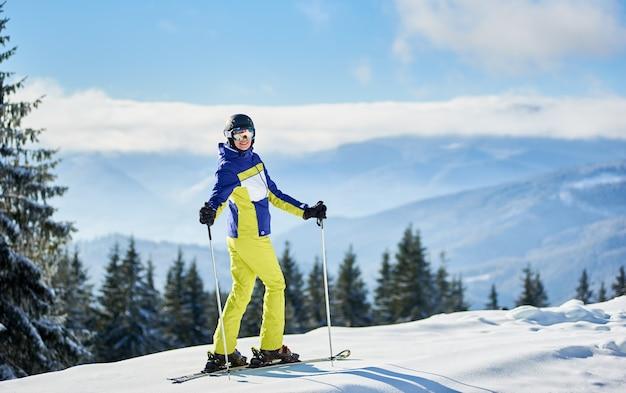 Gelukkige vrouwenskiër die zich voordeed op ski's