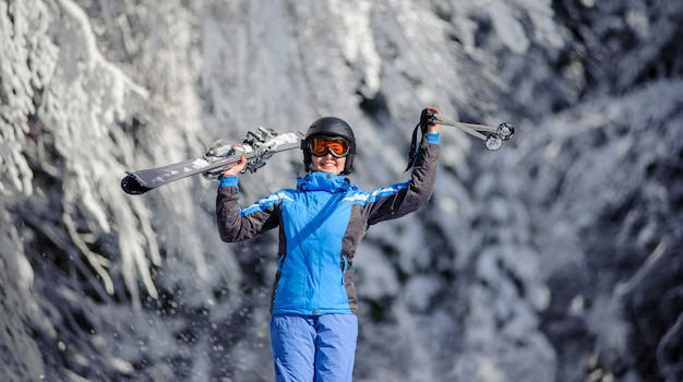 Gelukkige vrouwenskiër op een skihelling in het bos