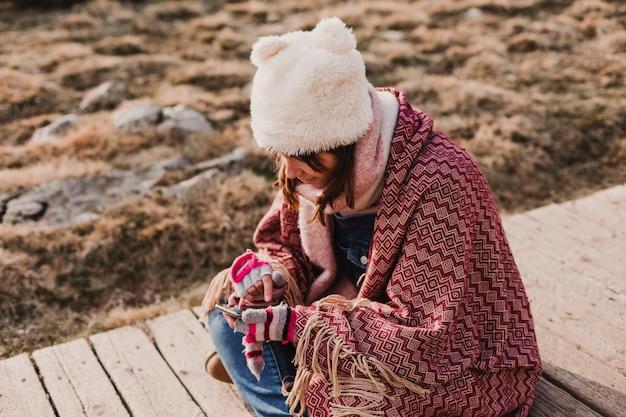 Gelukkige vrouwenst zonsondergang in aard in de herfst die mobiele telefoon met behulp van die met een deken wordt behandeld. plezier buitenshuis