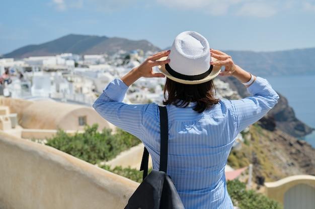 Gelukkige vrouwentoerist die in hoed met rugzak landschap van het eiland santorini bekijken