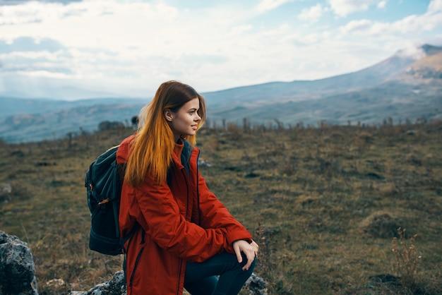 Gelukkige vrouwentoerist ging zitten om uit te rusten op een weiland in de bergen in de natuur