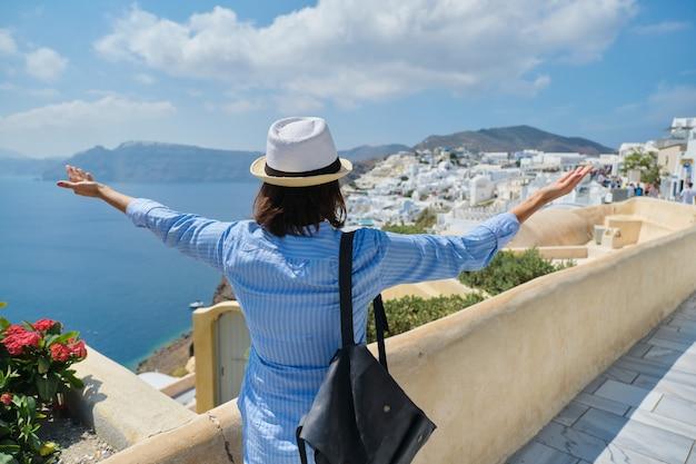 Gelukkige vrouwentoerist met opgeheven wapens, emotie van het geluk van het vrijheidssucces. achter mening van wijfje met hoedenrugzak, landschap van grieks eiland santorini, oia