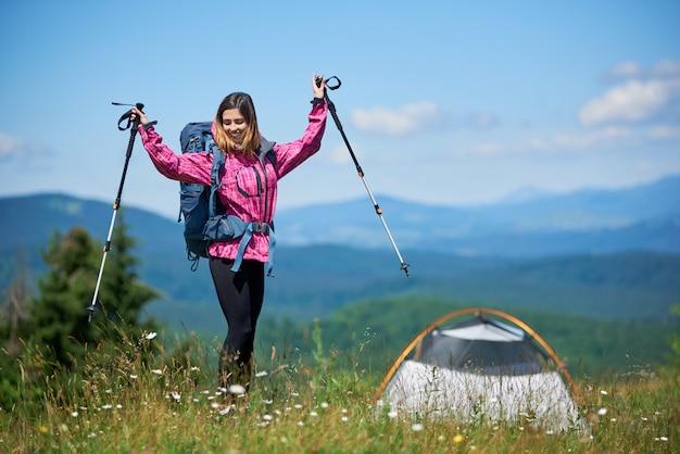 Gelukkige vrouwentoerist met rugzak en trekkingstokken dichtbij tent