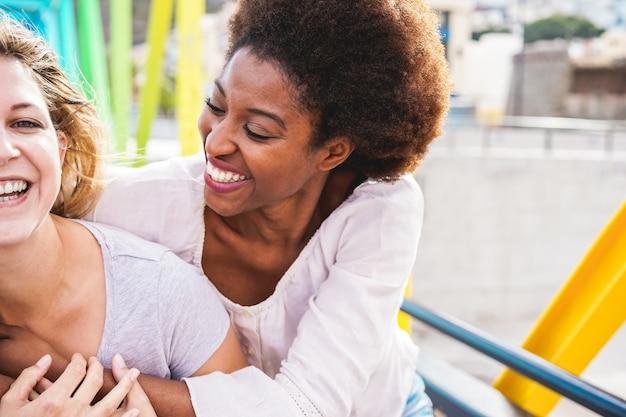 Gelukkige vrouwenvrienden die en op kleurrijke brug lachen lopen