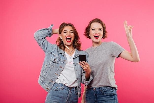Gelukkige vrouwenvrienden die mobiele telefoon het luisteren muziek met behulp van