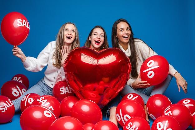 Gelukkige vrouwenvrienden poseren met rode hartvormige ballon en luchtballen met procent en verkoop belettering op blauwe achtergrond