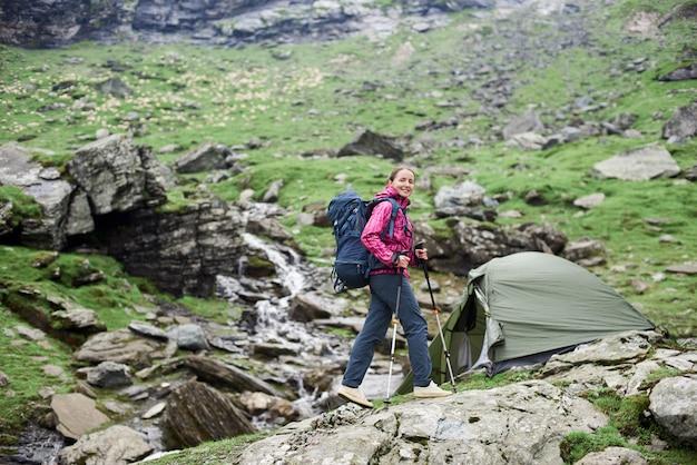 Gelukkige vrouwenwandelaar die aan de camera glimlacht die in de bergenvallei loopt