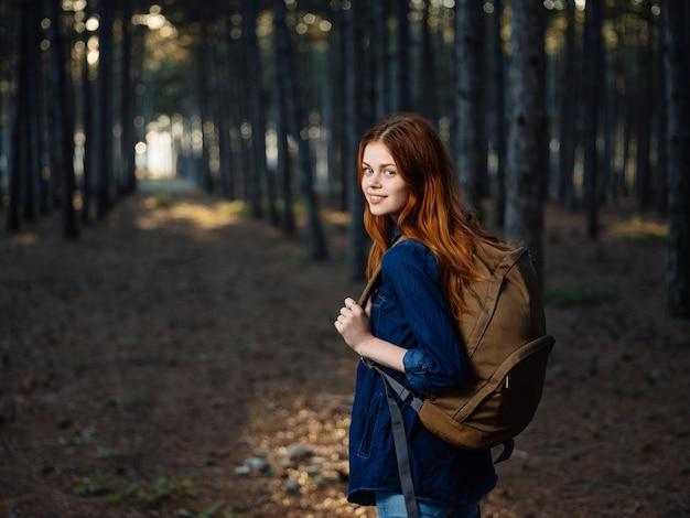 Gelukkige vrouwenwandelaar in het bos met een rugzak op zijn rug in de herfst op aard.