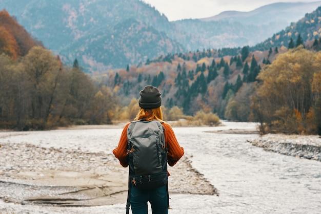 Gelukkige vrouwenwandelaar met een rugzak op de rivieroever kijkt in de bergen en de herfstbosnatuur
