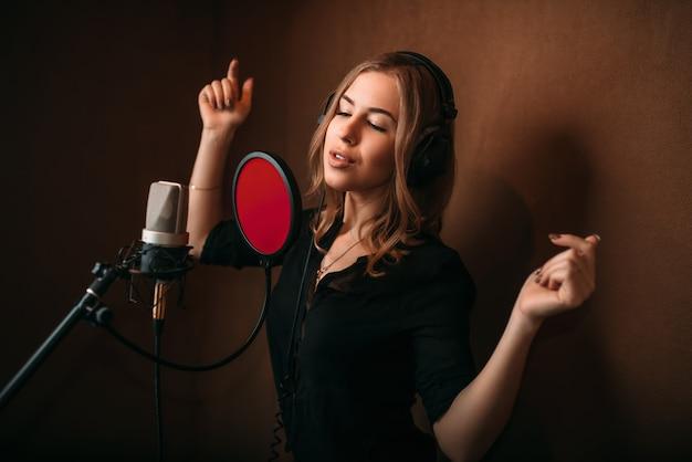 Gelukkige vrouwenzanger in hoofdtelefoons tegen microfoon, liedverslag in muziekstudio.