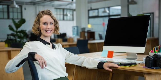 Gelukkige vrouwenzitting bij bureau