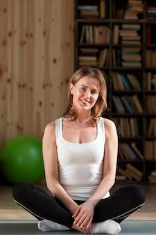 Gelukkige vrouwenzitting bij yogamat het stellen