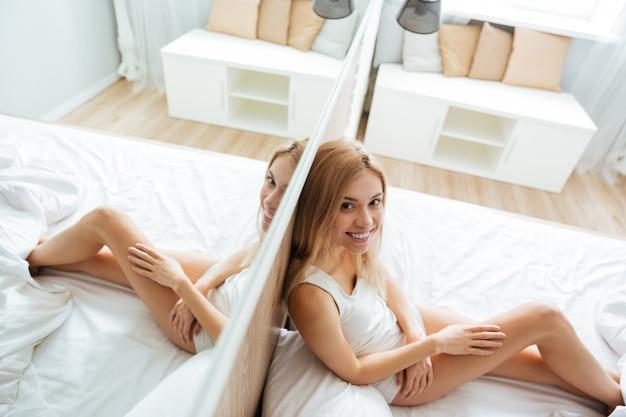 Gelukkige vrouwenzitting dichtbij de spiegel op bed in slaapkamer