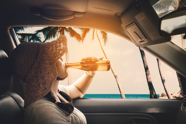 Gelukkige vrouwenzitting in de auto en reizende zomer op het overzeese rusten en de speciale dag aan vakantie.