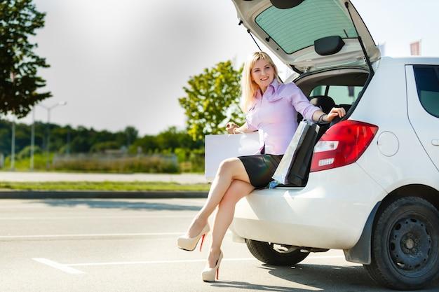 Gelukkige vrouwenzitting in een open boomstam van een nieuwe auto met het winkelen zakken