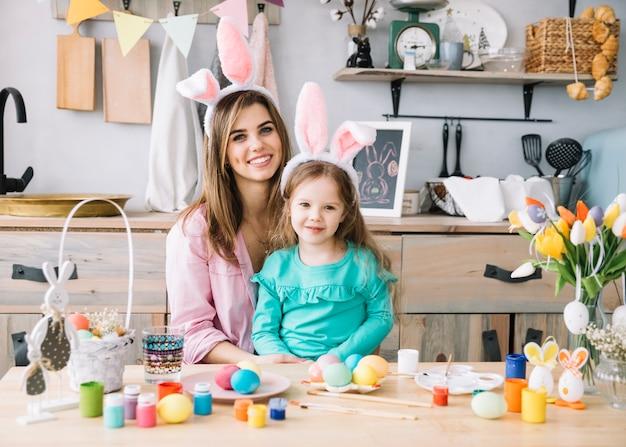 Gelukkige vrouwenzitting met dochter in konijntjesoren dichtbij paaseieren