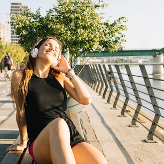 Gelukkige vrouwenzitting op bank die aan muziek luistert