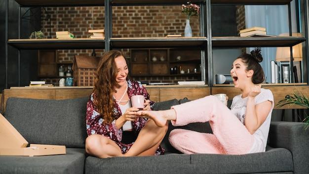 Gelukkige vrouwenzitting op bank die de voeten van haar vriend tikt