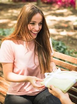 Gelukkige vrouwenzitting op bank die gift van haar vriend ontvangt
