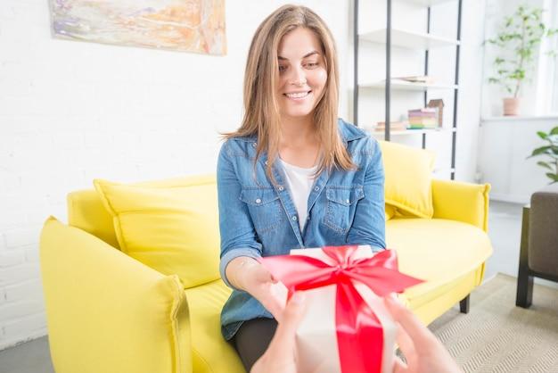 Gelukkige vrouwenzitting op gele bank die valentijnskaartgift ontvangt