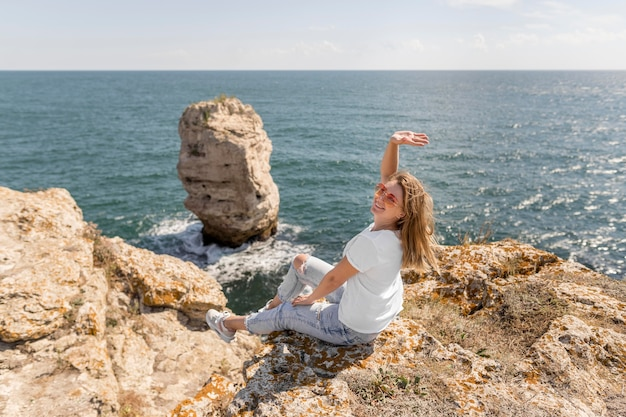 Gelukkige vrouwenzitting op rotsen