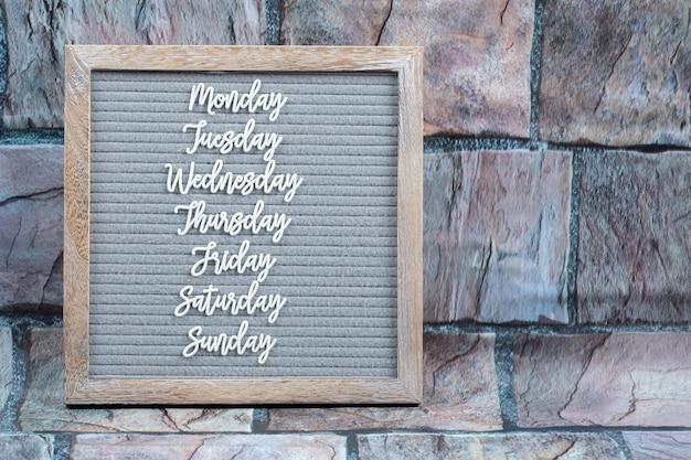 Gelukkige weekdagen poster geschreven met lettersymbolen op het grijze weefsel