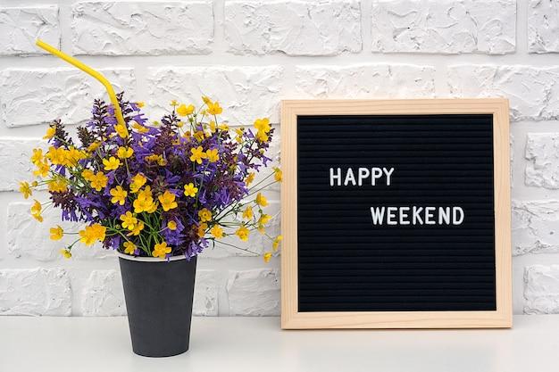 Gelukkige weekendwoorden op zwart brievenraad en boeket van gele paardebloemenbloemen