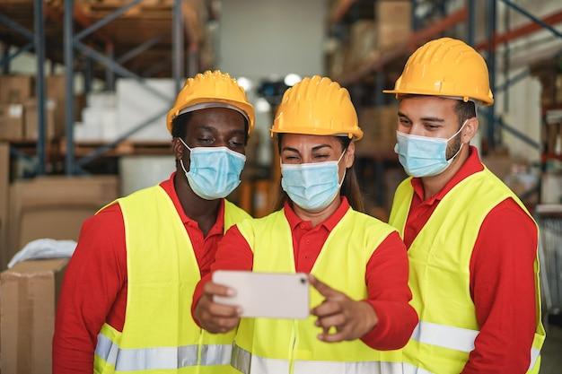 Gelukkige werknemer neemt selfie in magazijn terwijl hij veiligheidsmaskers draagt tijdens de uitbraak van het coronavirus
