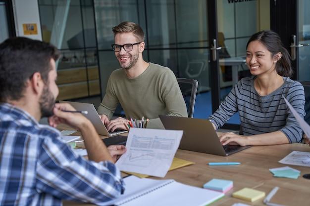 Gelukkige werknemers over gesprek in vergaderruimte