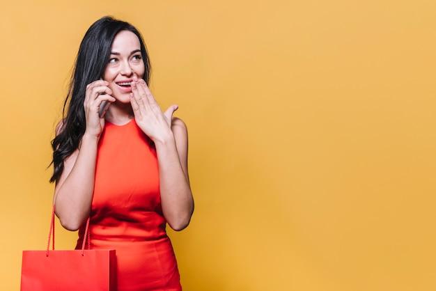 Gelukkige winkelende vrouw die telefoongesprek heeft