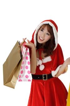 Gelukkige winkelende vrouw met zakken in kleren van de kerstman.