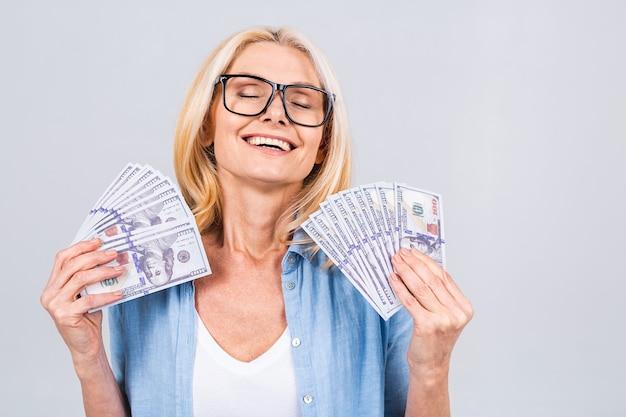 Gelukkige winnaar! afbeelding van een volwassen senior gelukkige oude vrouw die geïsoleerd staat over een witte muurachtergrond en geld vasthoudt.