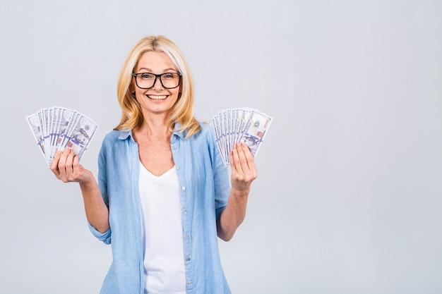 Gelukkige winnaar! afbeelding van een volwassen senior gelukkige oude vrouw die geïsoleerd staat over een witte muurachtergrond, kijkend naar de camera die geld vasthoudt.