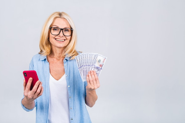 Gelukkige winnaar! afbeelding van volwassen gelukkig senior vrouw staande geïsoleerd over witte achtergrond muur kijken camera aanhouden van geld met behulp van mobiele telefoon.